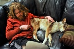 Chad Jukes sleeps on the couch with his dog Shiela at Chad Butrick's residence in Arvada, Colo., on March 8, 2010.